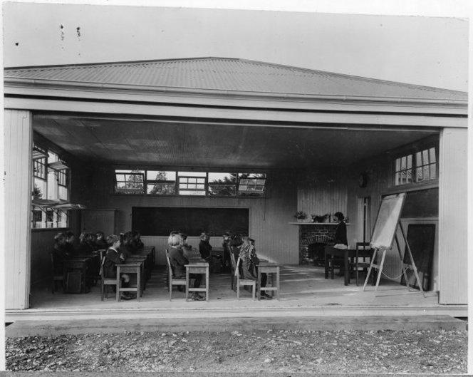 Photograph of an open air classroom, Fendalton School, Christchurch, taken circa 1924 by an unidentified photographer. Primary school children sit in rows at their desks, facing a teacher and a blackboard.