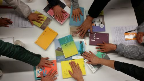 hands reaching for Korean books